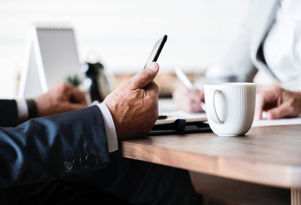 Persoon kijkt op smartphone tijdens business meeting